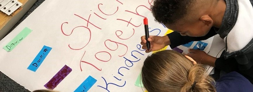 Students writing on Stick Together Kindness Matters Banner