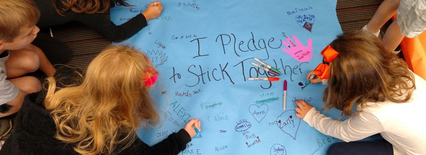 Photo of elementary students writing a Stick Together Pledge for Kindness Day