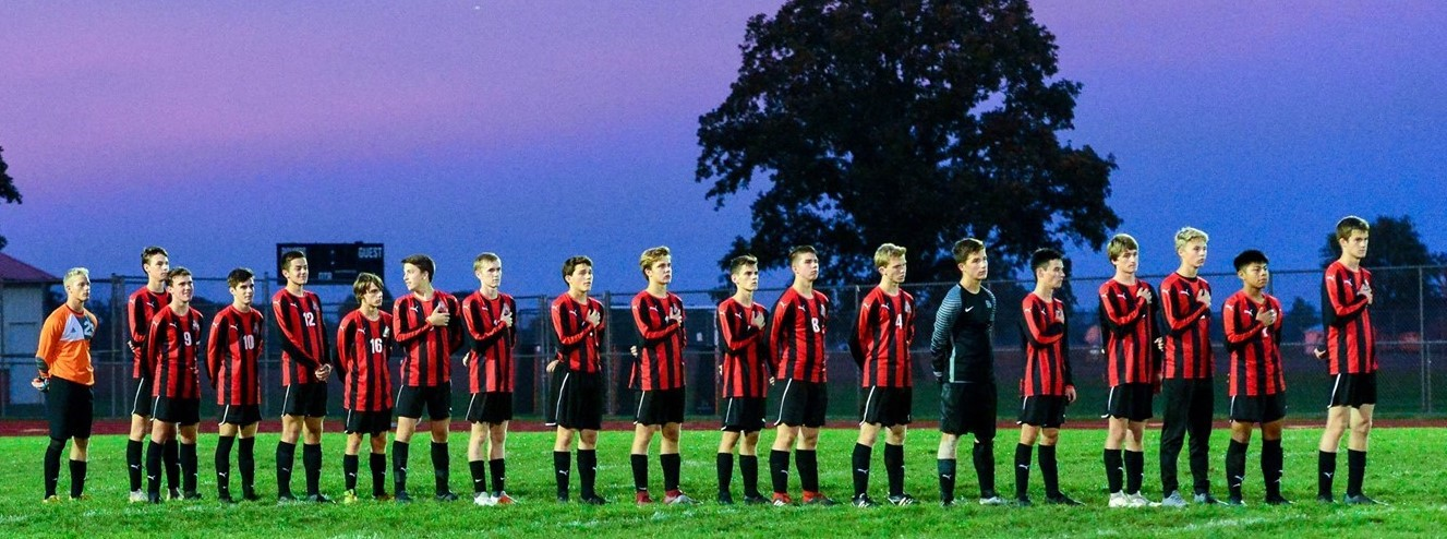 Photo of boys soccer team standing in a row on the soccer field for the National Anthem