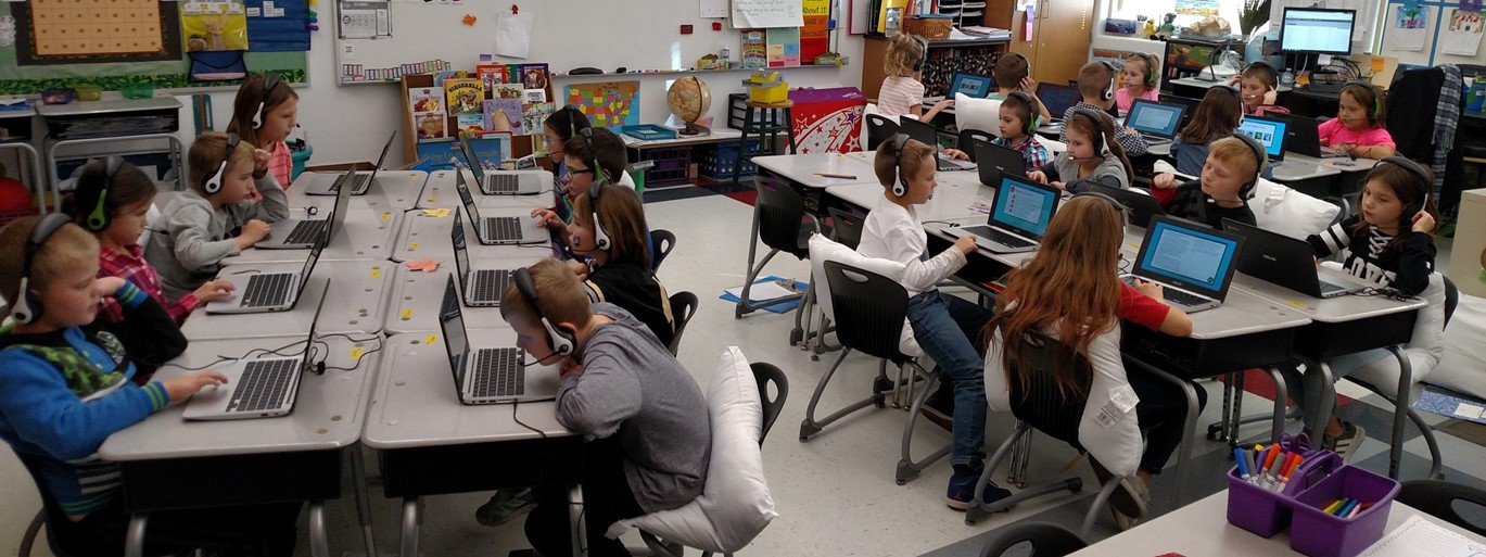 Photo of elementary students wearing headphones in classroom and working at computers