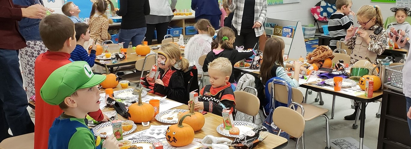 Photo of elementary students in costume eating lunch in their classroom