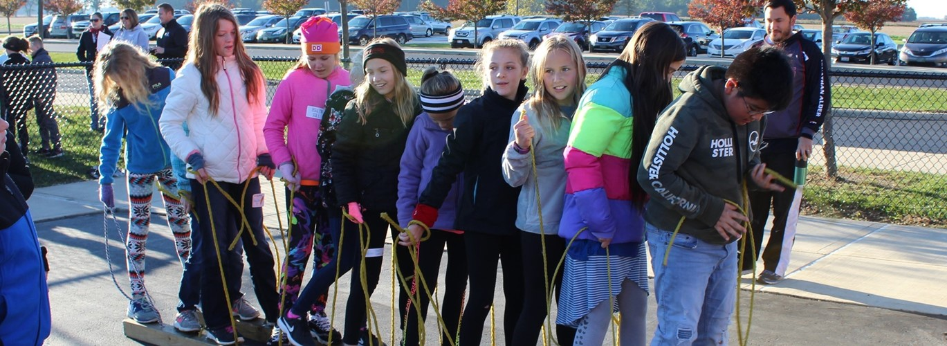 Photo of middle school students doing team building exercises outside