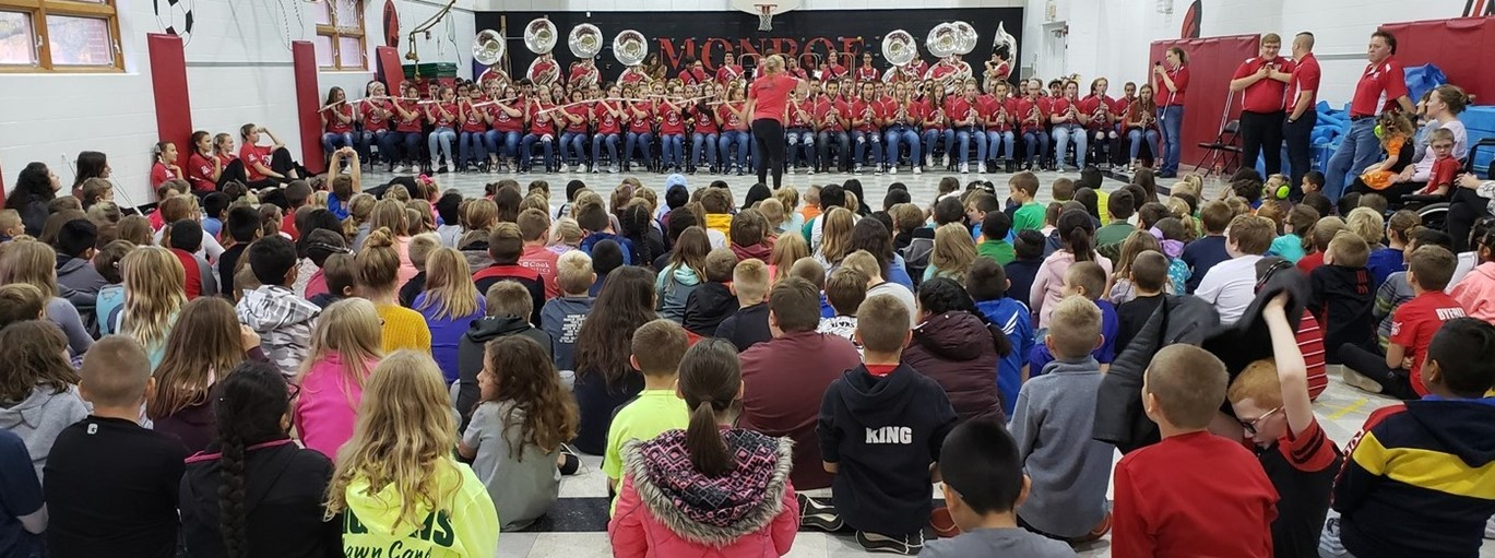 Photo of Monroe Elementary students listening to the marching band