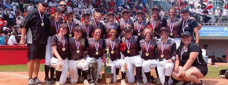 Photo of softball team with medals and trophy after winning state championship