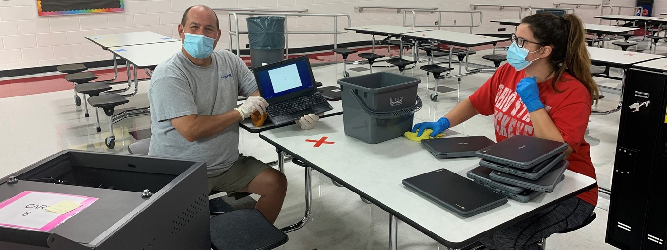 Picture of our HS Custodians cleaning chromebooks